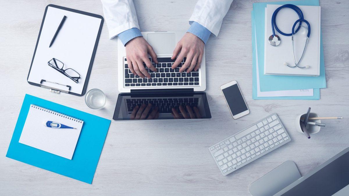 Arzt am PC beim Schreiben eines Befundes für die radiologische Zweitmeinung